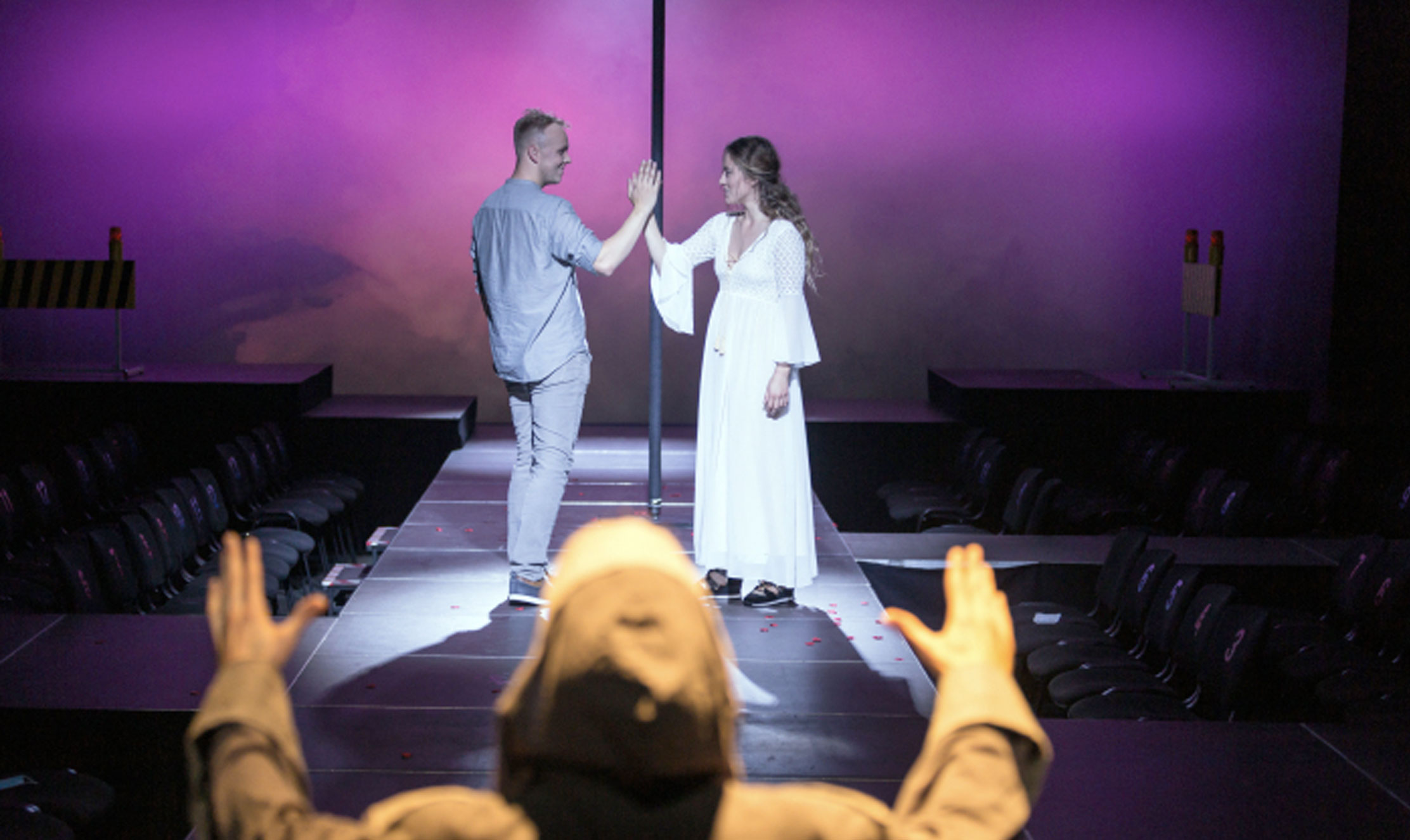 On a stage, a man and woman dressed in light colours stand facing each other and clasping hands.