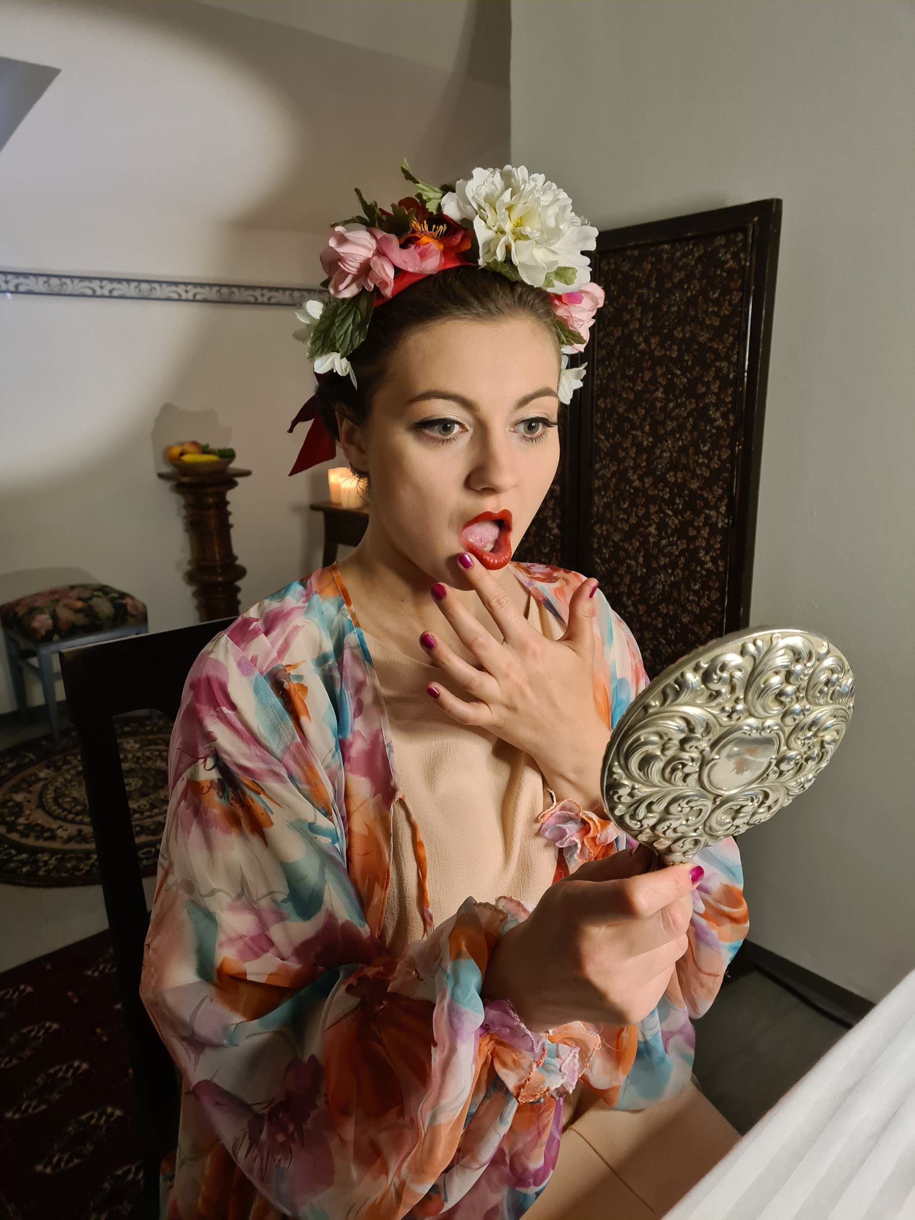 A woman wearing a flower garland in her hair checks her red lipstick in a handheld mirror. She is sat in a bedroom.